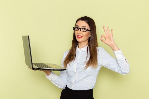 Vorderansicht der weiblichen büroangestellten im weißen hemd und im schwarzen rock, die ihren laptop mit lächeln auf grüner wand halten und verwenden