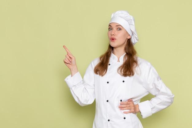 Vorderansicht der weiblichen köchin im weißen kochanzug, der auf der grünen wand aufwirft