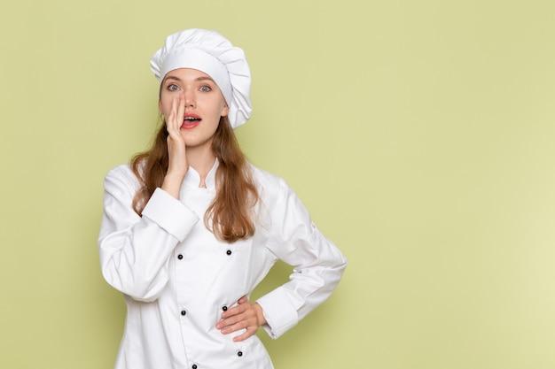 Vorderansicht der weiblichen köchin im weißen kochanzug, der auf grüner wand aufwirft und flüstert