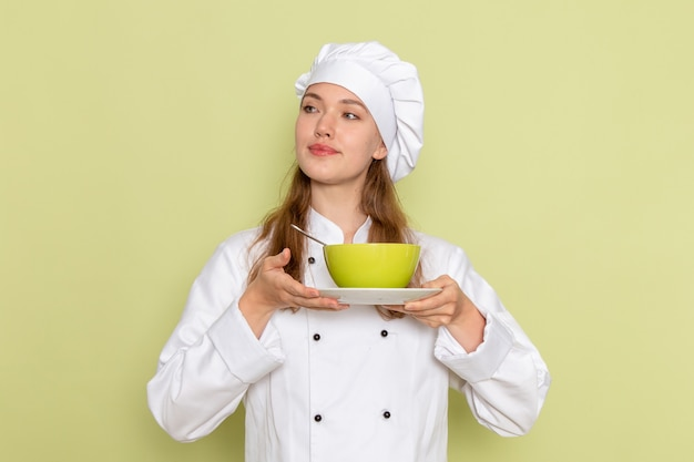 Vorderansicht der weiblichen köchin im weißen kochanzug, der grünen teller mit teller auf der grünen wand hält