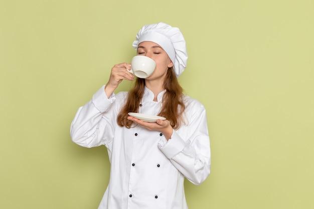 Vorderansicht der weiblichen köchin im weißen kochanzug, der kaffee auf grüner wand trinkt