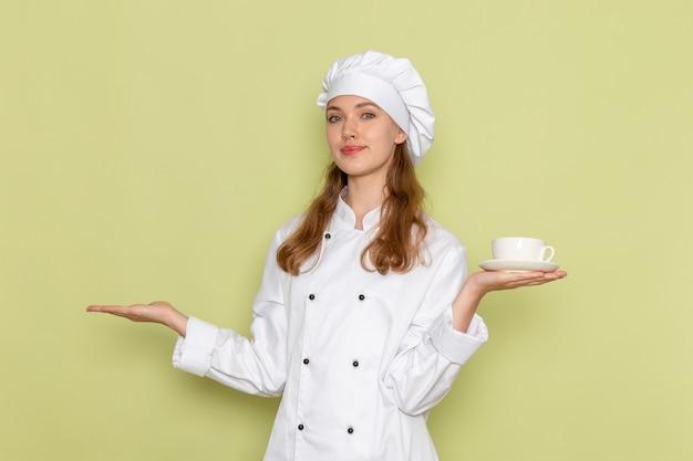 Vorderansicht der weiblichen köchin im weißen kochanzug lächelnd und hält weiße tasse mit kaffee auf grüner wand