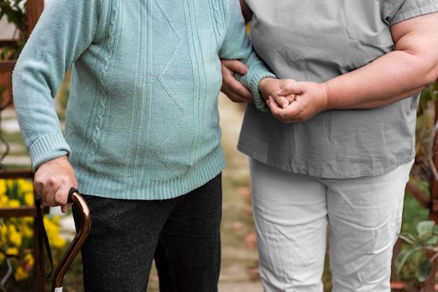 Vorderansicht der weiblichen krankenschwester, die der älteren frau beim gehen hilft