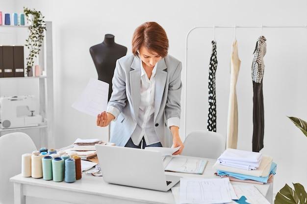 Vorderansicht der weiblichen modedesignerin, die kleidungslinienpläne im atelier berät