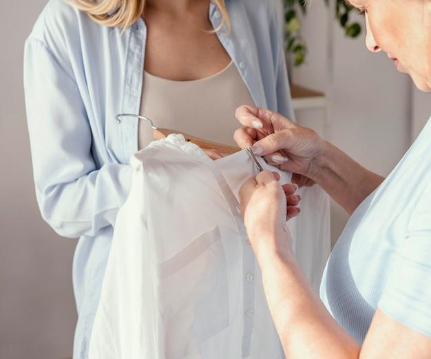 Vorderansicht der weiblichen näherin, die stoff für kleidungsstück wählt