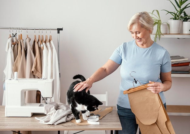 Vorderansicht der weiblichen näherin im studio mit katze