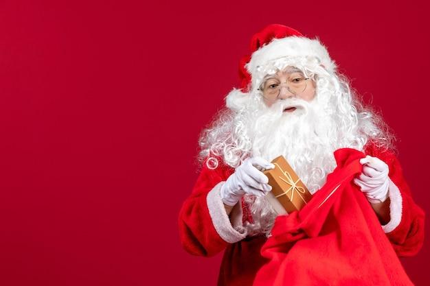 Vorderansicht der weihnachtsmann, der ein geschenk aus einer tasche voller geschenke für kinder auf dem roten gefühl des neuen jahres hält
