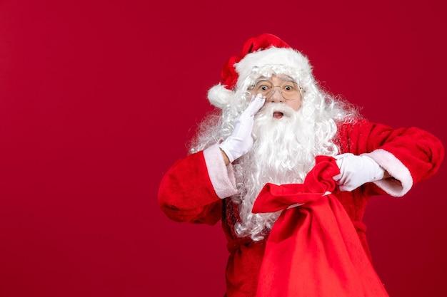 Vorderansicht der weihnachtsmann, der eine tasche voller geschenke für kinder an roten feiertagen weihnachtsgefühlen öffnet