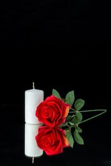 Vorderansicht der weißen kerze mit roter rose auf schwarz