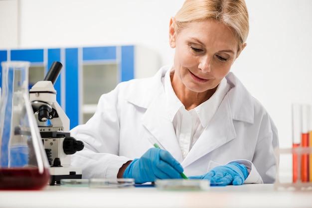 Vorderansicht der wissenschaftlerin, die etwas im labor aufschreibt