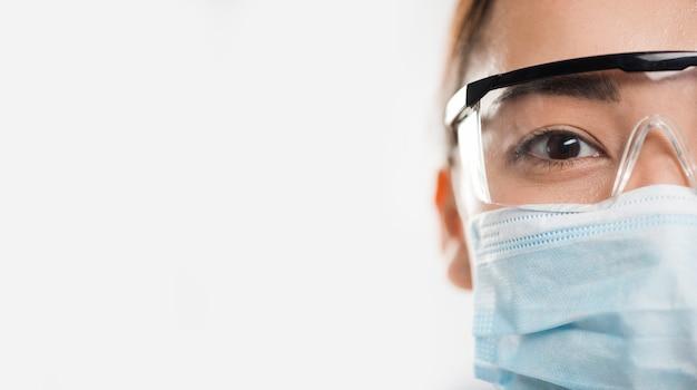 Vorderansicht der wissenschaftlerin, die medizinische maske mit kopienraum trägt