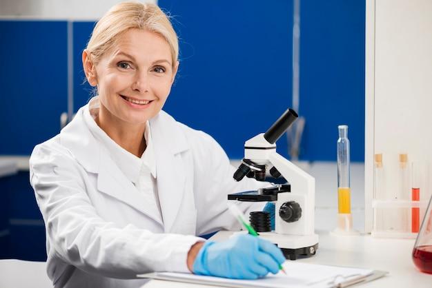 Vorderansicht der wissenschaftlerin, die mit mikroskop im labor aufwirft