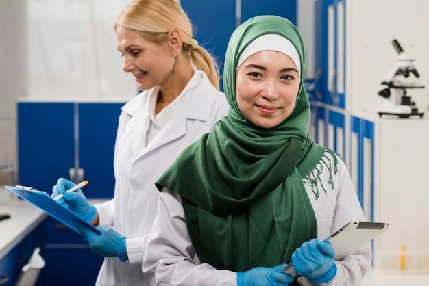 Vorderansicht der wissenschaftlerin mit hijab, der im labor mit kollegin aufwirft