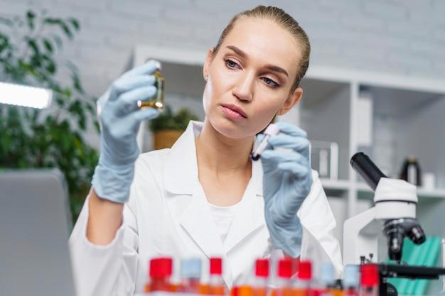 Vorderansicht der wissenschaftlerin mit medizin mit reagenzgläsern und mikroskop