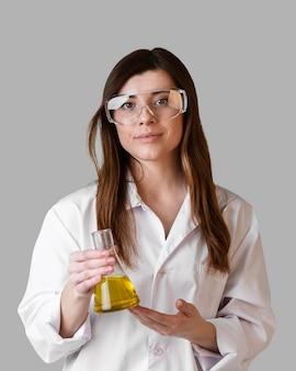 Vorderansicht der wissenschaftlerin mit schutzbrille, die reagenzglas hält
