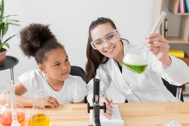 Vorderansicht der wissenschaftlerin und des mädchens, die spaß mit chemieexperimenten haben