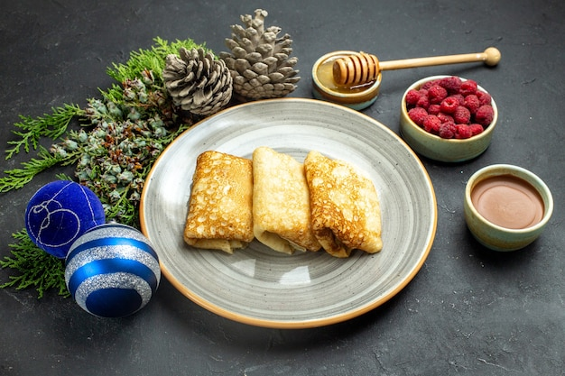 Vorderansicht des abendessenhintergrundes mit köstlichem pfannkuchenhonig und schokoladenhimbeer- und nadelbaumkegel neben neujahrszubehör auf schwarzem hintergrund