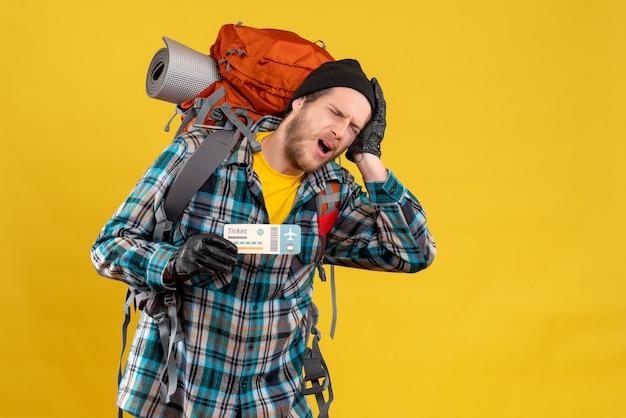 Vorderansicht des abgestumpften jungen rucksacktouristen mit dem schwarzen hut, der kopf und reiseticket hält Kostenlose Fotos