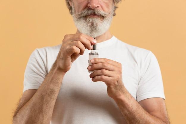 Vorderansicht des älteren bärtigen mannes, der serum hält