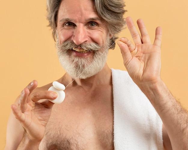 Vorderansicht des älteren bärtigen mannes mit zahnseide