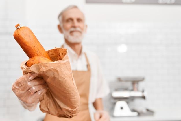 Vorderansicht des älteren männlichen metzgers, der fleischprodukte gibt. selektiver fokus der würste im papierpaket in der hand des fröhlichen älteren mannes, der im supermarkt steht, auf weißem hintergrund.