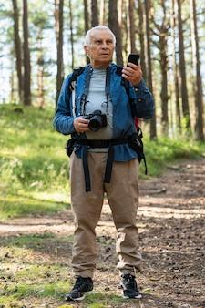 Vorderansicht des älteren mannes, der natur mit smartphone und kamera erkundet