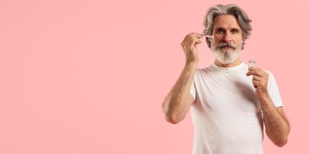 Vorderansicht des älteren mannes mit bart unter verwendung des serums