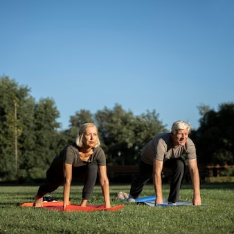 Vorderansicht des älteren paares, das draußen yoga macht