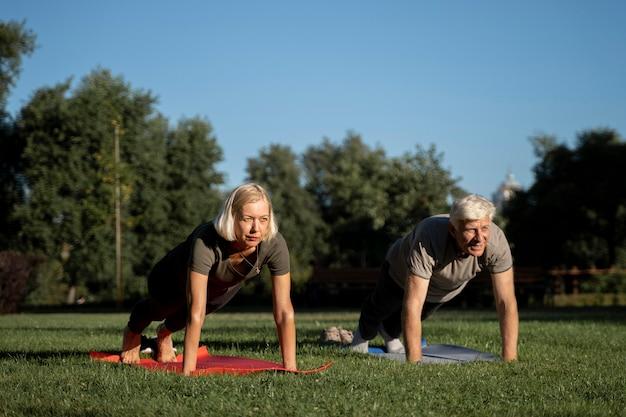 Vorderansicht des älteren paares, das yoga im freien tut
