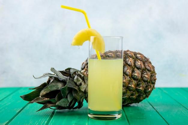 Vorderansicht des ananassaftes mit ananas auf grüner oberfläche und weißer oberfläche
