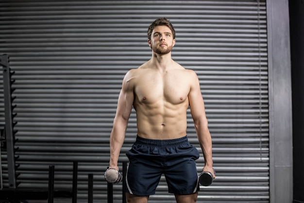 Vorderansicht des anhebenden gewichts des ernsten mannes an der turnhalle