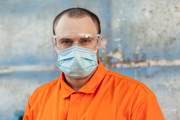 Vorderansicht des arbeiters in uniform mit medizinischer maske