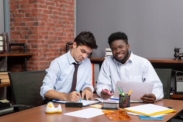 Vorderansicht des arbeitsprozesses zwei geschäftsleute, die an der schreibtischsocke sitzen foto