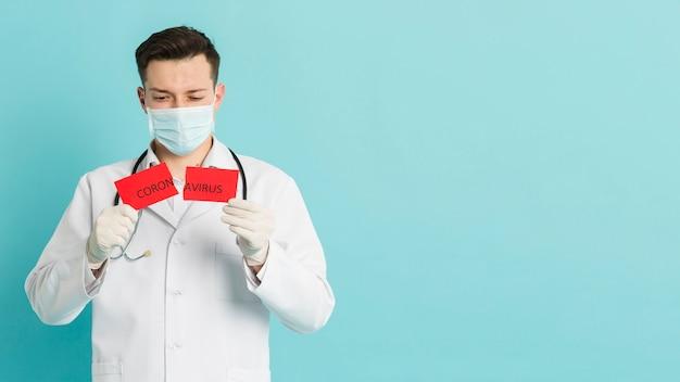 Vorderansicht des arztes, der zerrissenes papier mit coronavirus und kopienraum hochhält