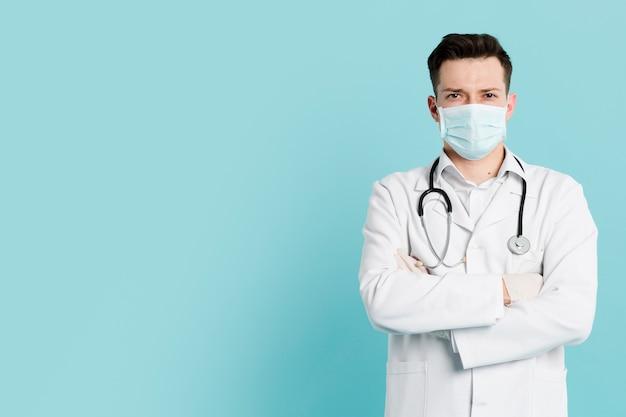 Vorderansicht des arztes mit der medizinischen maske, die mit verschränkten armen aufwirft