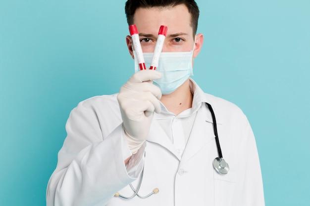 Vorderansicht des arztes mit der medizinischen maske, die vacutainer hält