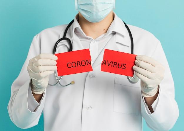Vorderansicht des arztes mit der medizinischen maske, die zerrissenes papier mit coronavirus hält