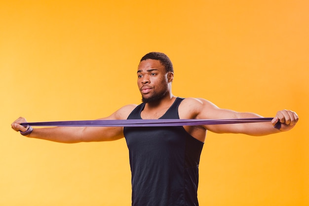 Vorderansicht des athletischen mannes in der turnhallenausstattung mit widerstandband