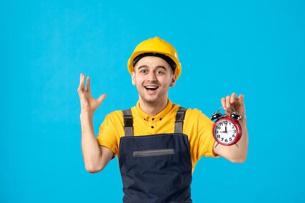 Vorderansicht des aufgeregten männlichen arbeiters in der gelben uniform mit uhren auf einer blauen oberfläche