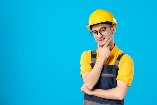 Vorderansicht des aufstellens des männlichen baumeisters in der uniform und im helm auf blau