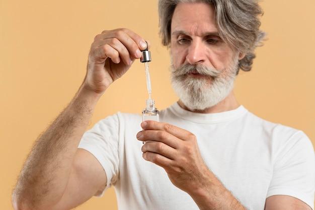 Vorderansicht des bärtigen älteren mannes, der serum hält
