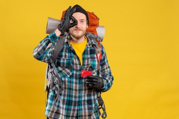 Vorderansicht des bärtigen jungen rucksacktouristen mit dem schwarzen hut, der kreditkarte hält, das ok zeichen macht