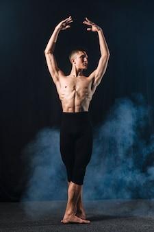 Vorderansicht des ballerinos in den strumpfhosen und im rauche