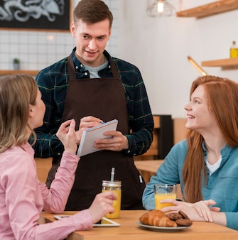 Vorderansicht des barista, der eine bestellung entgegennimmt