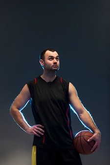 Vorderansicht des basketball-spielers mit ball- und kopienraum