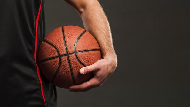 Vorderansicht des basketballs gehalten vom spieler nah an hüfte