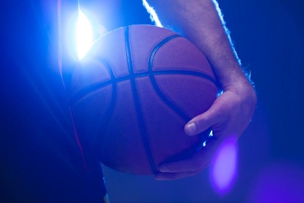 Vorderansicht des basketballs gehalten vom spieler