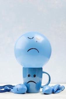 Vorderansicht des bechers und des ballons mit stirnrunzeln für blauen montag