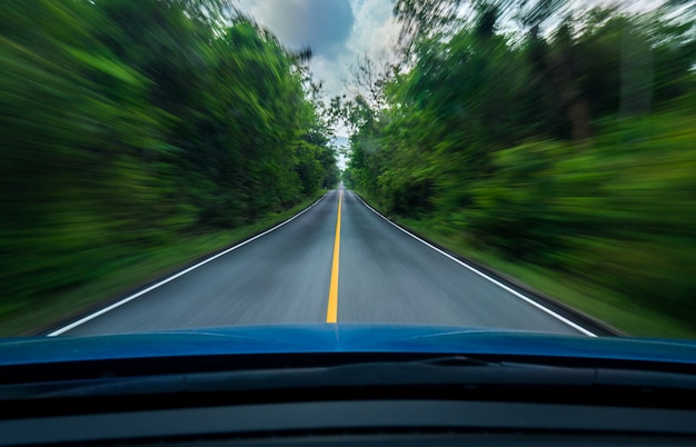 Vorderansicht des blauen autos, das mit hoher geschwindigkeit auf der mitte der asphaltstraße mit weißer und gelber linie fährt