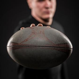 Vorderansicht des defokussierten männlichen rugbyspielers, der ball hält